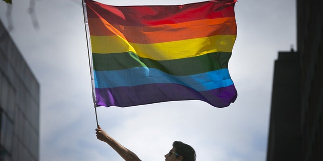 June 28, 2015: A man waves a rainbow flag while observing a gay pride parade in San Francisco, Calif.