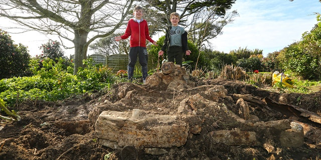 Brothers, Joe, 9 and Jake Ward, 6 with the buried Daimler which they discovered in their garden at a property in Rue du Felconte on Guernsey. See SWNS story SWCAR: These pictures show a rockery in a family's garden which turned out to be a buried 70-year-old CAR. Tracy and Chris Ward bought their home last November, but have only just set about tackling the garden. In the centre of their small plot there was an ornate rockery - or so they thought. When they started digging out the rockery they started to uncover bits of metal, and before long they had unearthed the remains of a 70-year-old Daimler Consort.