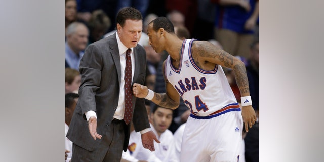 Kansas coach Bill Self talks with guard Travis Releford (24) during the first half of an NCAA college basketball game against TCU in Lawrence, Kan., Saturday, Feb. 23, 2013. (AP Photo/Orlin Wagner)