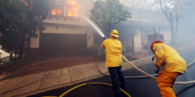 Los Angeles firefighters battle to contain flames on a burning home in the Bel Air district of Los Angeles, Wednesday.