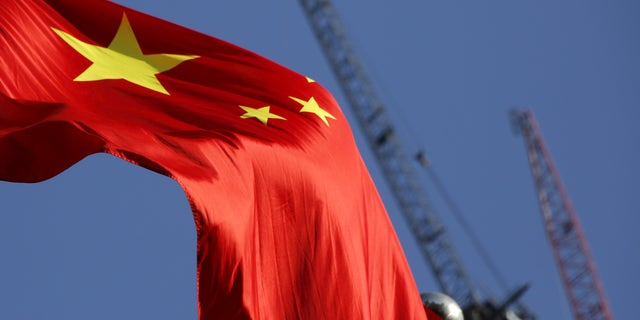 China's national flag is seen in front of cranes on a construction site at a commercial district in Beijing, China, January 26, 2016. REUTERS/Kim Kyung-Hoon - RTX240F5