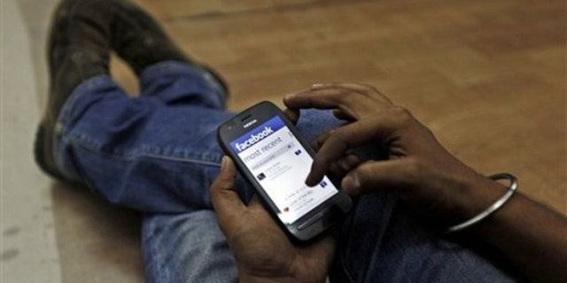 May 18, 2012: A man surfs the Facebook site on his mobile phone.