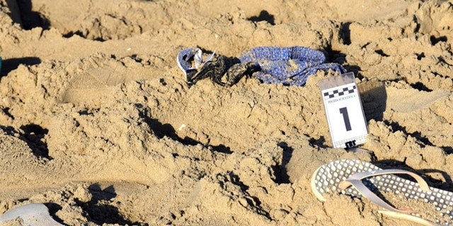 A pair of beach slippers lie in the sand where a gang rape of a Polish tourist and the beating of her partner took place in Rimini, Italy.