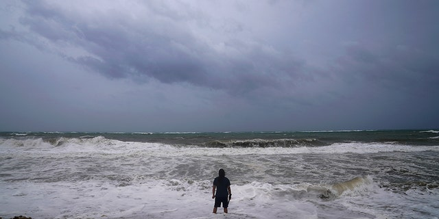 A man stands in the water at the beach ahead of Hurricane Irma's expected arrival in Fort Lauderdale, Florida, U.S., September 9, 2017. REUTERS/Carlo Allegri - RC12C86B5960