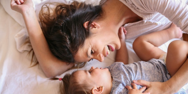 Young mother playing with her baby girl playing in bed. Space for copy.
