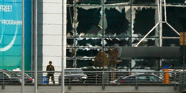 A soldier stands near broken windows after explosions at Zaventem airport near Brussels, Belgium.