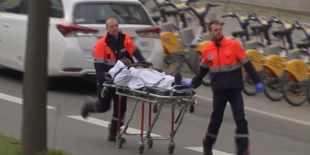 In this image taken from TV an injured person is evacuated as emergency services attend the scene after an explosion in a main metro station in Brussels.