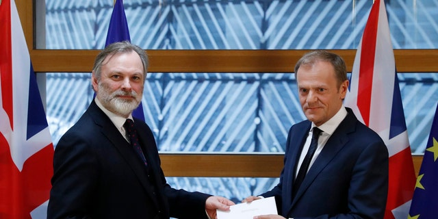 Britain's permanent representative to the European Union Tim Barrow, left, hand delivers British Prime Minister Theresa May's Brexit letter in notice of the UK's intention to leave the bloc under Article 50 of the EU's Lisbon Treaty to EU Council President Donald Tusk, in Brussels, Belgium, Wednesday, March 29, 2017. Barrow hand-delivered the letter signed by Britain's Prime Minister Theresa May that will formally trigger the beginning of Britain's exit from the European Union. (Yves Herman/Pool Photo via AP)