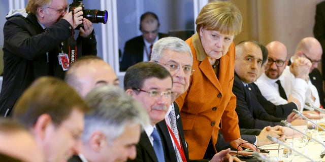 German Chancellor Angela Merkel, center, takes her seat during a lunch with other leaders at an EU summit in Brussels.