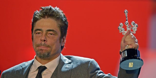 September 26, 2014. Puerto Rican actor Benicio Del Toro holds up his trophy after receiving the Donostia Award for career achievement on the eighth day of the 62nd San Sebastian Film Festival.