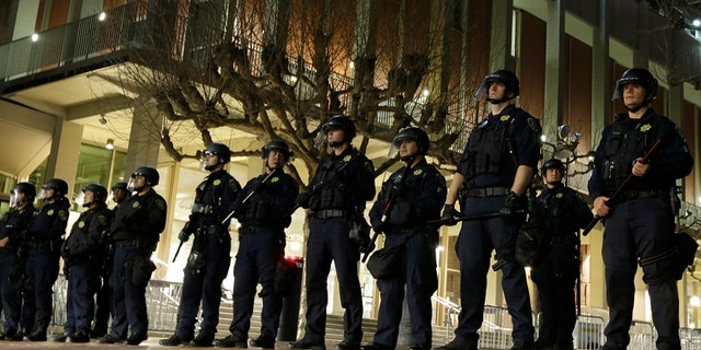 University of California at Berkeley police guard the building where Breitbart News editor Milo Yiannopoulos was to speak Wednesday, Feb. 1, 2017, in Berkeley, Calif. A small group of people with their faces covered broke windows, hurled fireworks at police officers and threw smoke bombs, prompting UC Berkeley officials to cancel Yiannopoulos's talk.