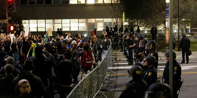 Protesters chant in front of a police line outside Berkeley Police Department headquarters during a march against the New York City grand jury decision not to indict in the death of Eric Garner, in December 2014.