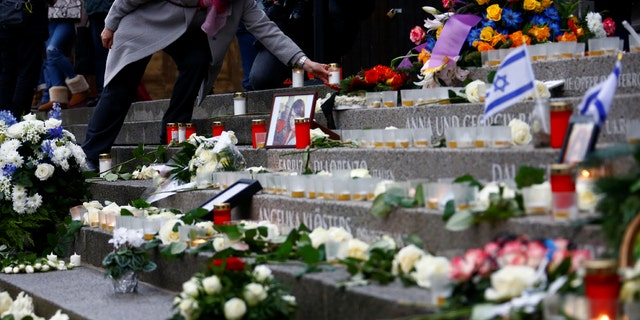 A woman lights a candle at the memorial at the site of last year's truck attack in a Christmas market, which killed 12 people and injured many others, at Breitscheidplatz square in Berlin, Germany, December 19, 2017.