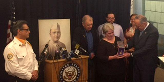 Sen. Charles Schumer of New York presents lost Purple Heart to family of World War II Staff Sgt. Bernard J. McNamara at press conference Sunday.