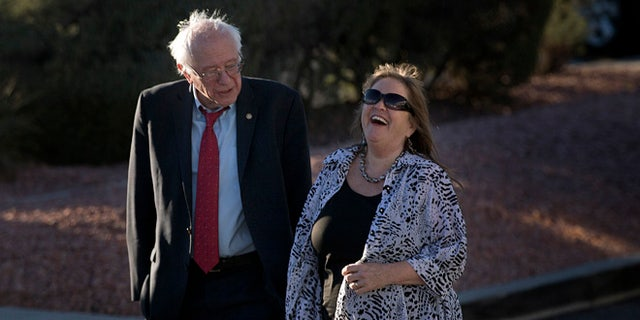 Democratic presidential candidate Sen. Bernie Sanders, I-Vt., and wife, Jane, share a light moment as they stroll around a parking lot after arriving at the at the McCarran International Airport Thursday, Feb. 18, 2016, in Las Vegas. (AP Photo/Jae C. Hong)