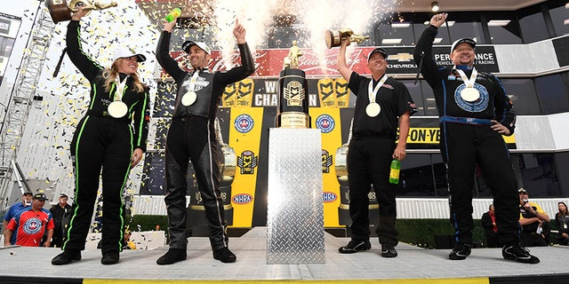 In this photo provided by the NHRA, the four Auto Club NHRA Finals drag races winners from left, Brittany Force, Top Fuel, Eddie Krawiec, Pro Stock Motorcycle, Bo Butner, Pro Stock, and Robert Hight, Funny Car, celebrate on state at Auto Club Raceway, Sunday, Nov. 12, 2017, in Pomona, Calif. (Marc Gewertz/NHRA via AP)