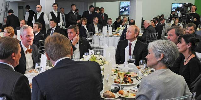 FILE- In this file photo taken on Thursday, Dec. 10, 2015, Russian President Vladimir Putin, center right, with retired U.S. Lt. Gen. Michael T. Flynn, center left, and Serbian filmmaker Emir Kusturica, obscured second right, attend an exhibition marking the 10th anniversary of RT (Russia Today) 24-hour English-language TV news channel in Moscow, Russia. Flynn is widely reported Thursday Nov. 17, 2016, to be a potential contender to become national security advisor to U.S. president elect Donald Trump, although his appointment may be controversial. (Mikhail Klimentyev/Sputnik, Kremlin Pool Photo via AP, file)