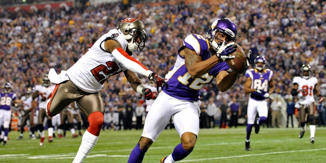 ADVANCE FOR WEEKEND EDITIONS, FEB. 16-17 - FILE - In this Oct. 25, 2013, file photo, Minnesota Vikings wide receiver Percy Harvin, right, catches an 18-yard touchdown pass ahead of Tampa Bay Buccaneers cornerback Eric Wright, left, during the first half of an NFL football game in Minneapolis. The Vikings have a quandary with Harvin: try to sign the talented but sometimes moody wide receiver to a long-term contract extension, let the last year of his current deal play out and brace for the potential distraction, or trade him.  (AP Photo/Jim Mone, File)