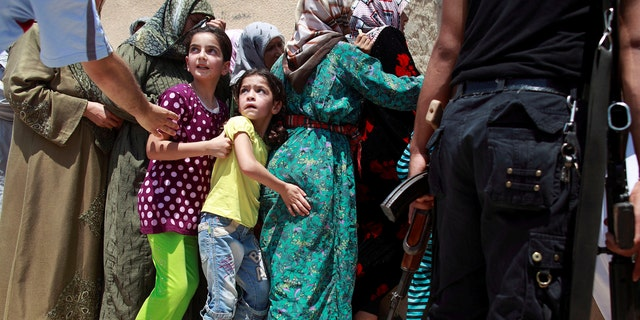 Girls queue to buy bread at the only bakery serving the outskirts of Idlib province, Syria August 1, 2012.