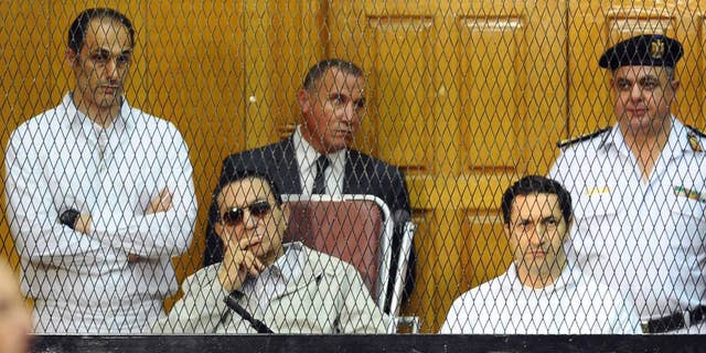 FILE - In this file photo taken Saturday, Sept. 14, 2013, former Egyptian President Hosni Mubarak, seated left, and his two sons, Gamal Mubarak, far left, and Alaa Mubarak attend a hearing in a courtroom at the Police Academy, Cairo, Egypt. The sons of Mubarak were ordered released on bail Thursday, Jan. 22, 2015, pending a retrial in the last case that was keeping them behind bars, opening the door for the release of the two for the first time since they were incarcerated in the wake of their father's ouster in 2011. (AP Photo/Mohammed al-Law, File)