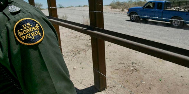 **FILE ** A U.S. Customs and Border Patrol agent is shown by the International border as a truck passes on the Mexican side of the border, in a  May 24, 2006 file photo, in Arizona. Sixty three miles of vehicle barriers are in place on the Arizona border to thwart smugglers trying to bring illegal immigrants or drugs into the country in vans, SUVs and trucks. Authorities look to have a total of 200 miles of barriers across the Southwest, mostly in Arizona and New Mexico, by the end of 2008. (AP Photo/Matt York, File)