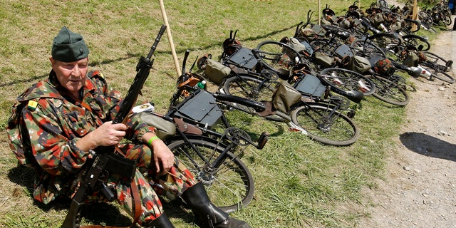File photo - A participant dressed as soldier of the former Swiss bicycle regiment rests during the Convoy-to-Remember 2010 meeting in the village of Birmenstorf, west of Zurich August 7, 2010. (REUTERS/Arnd Wiegmann)