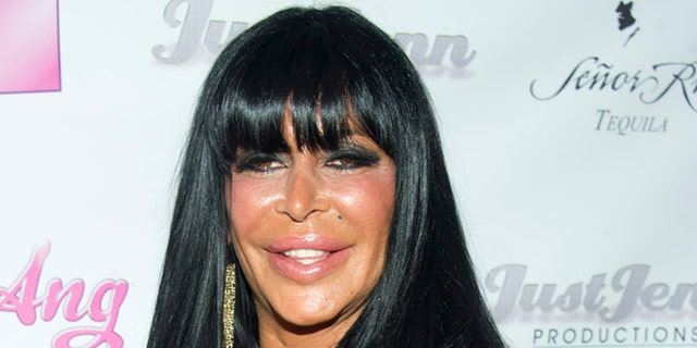"""July 8, 2012.  Angela Raiola, known as """"Big Ang,"""" and her dog Little Louie arrive to the premiere of her VH1 reality show """"Big Ang"""" in New York."""