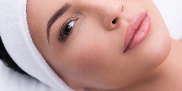 Top view close-up of beautiful woman with lengthened eyelashes. She is lying and looking at camera with confidence