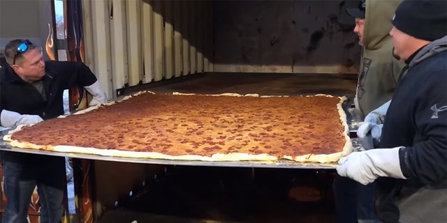 The six-foot-by-six-foot square pizza clocked in at 100 pounds of crust, sauce, cheese and pepperoni.
