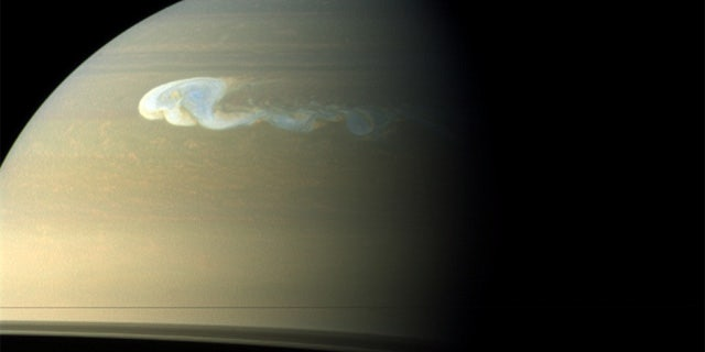 """An image of Saturn taken by the Cassini spacecraft shows a storm with a latitudinal and longitudinal extent of 10,000 km and 17,000 km, respectively. The latitudinal extent of the storm's head is approximately the distance from London to Cape Town. A """"tail"""" emerging from its southern edge extends further eastward."""