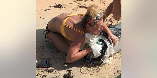 Police are looking to identify a woman who was seen hugging a bundle of marijuana that washed up on a Florida beach.