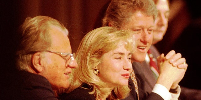 Rev. Billy Graham, left, sits with First Lady Hillary Clinton and President Bill Clinton at the head table during a prayer breakfast.