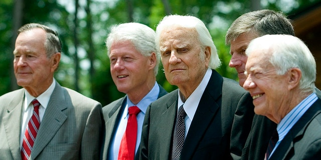 Former U.S. Presidents George H. W. Bush, left, and Bill Clinton, Billy Graham, and former President Jimmy Carter stand together. Graham was a spiritual adviser to each of the men.