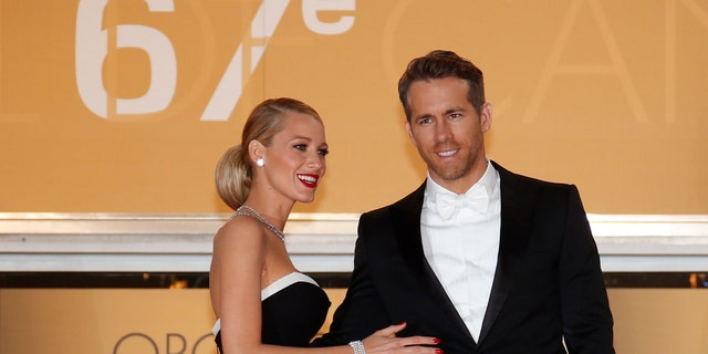 """Cast member Ryan Reynolds (R) and his wife actress Blake Lively pose on the red carpet as they arrive for the screening of the film """"Captives"""" (The Captive) in competition at the 67th Cannes Film Festival in Cannes May 16, 2014.                    REUTERS/Benoit Tessier (FRANCE  - Tags: ENTERTAINMENT)   - RTR3PJKX"""