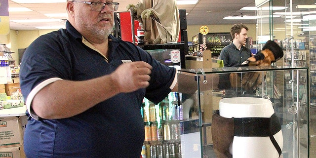 "Blockbuster Alaska General Manager Kevin Daymude moves a display case featuring the jockstrap worn by actor Russell Crowe in the 2005 movie ""Cinderella Man"" at a Blockbuster video store in Anchorage, Alaska."