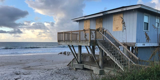 A boarded up home on North Topsail Beach in North Carolina as Hurricane Florence approaches in the distance.