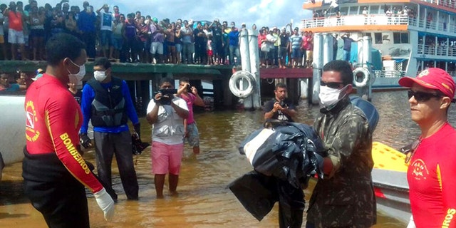 Residents watch rescue workers carry away bodies recovered after a boat that sank while it was traveling on the Xingu River.