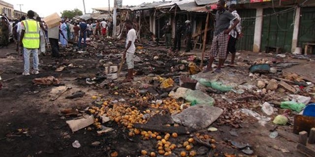 People gather on July 2, 2014, at the scene of a car bomb explosion, at the central market, in Maiduguri, Nigeria, the birthplace of terror group Boko Haram. (AP Photo/Jossy Ola)