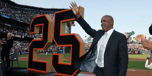 Former San Francisco Giants player Barry Bonds waves during a ceremony to retire his jersey number before a baseball game between the Giants and the Pittsburgh Pirates in San Francisco, Aug. 11, 2018.