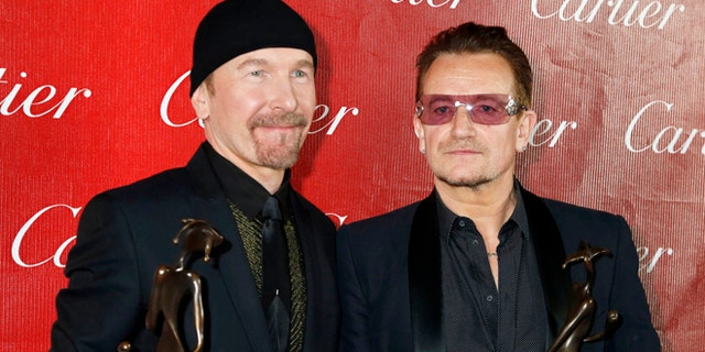 Bono (R) and the Edge of U2 pose backstage with the Sonny Bono Visionary Award they received at the 2014 Palm Springs International Film Festival Awards Gala in Palm Springs, California January 4, 2014. REUTERS/Fred Prouser (UNITED STATES - Tags: ENTERTAINMENT) - RTX172NH