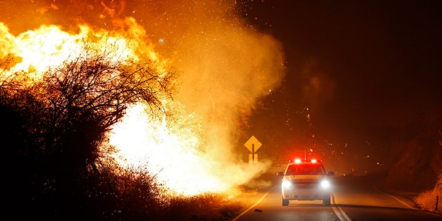 Dec. 7, 2017: Fire personnel drive along West Lilac Road as the Lilac Fire burns near Bonsall, Calif., in San Diego County.