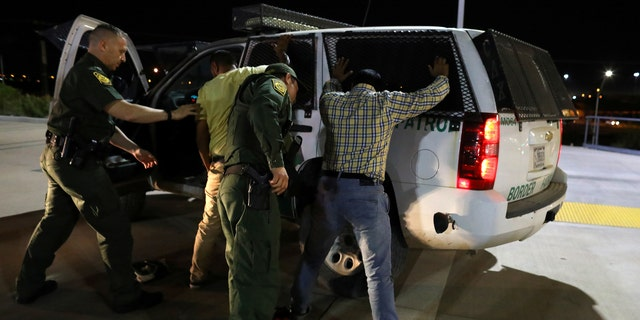 Border patrol agents make an arrest.