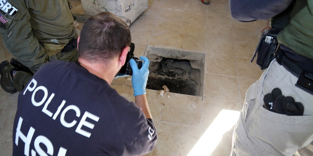 March 23, 2016: This photo provided by U.S. Immigration and Customs Enforcement shows an investigator photographing the terminus of a tunnel at a newly-built home in Calexico, Calif., that runs the length of four football fields to a restaurant in Mexicali, Mexico.