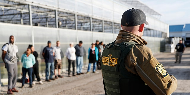 Immigration agents stand guard alongside suspects taken into custody during an immigration sting at Corso's Flower and Garden Center Tuesday in Castalia, Ohio.