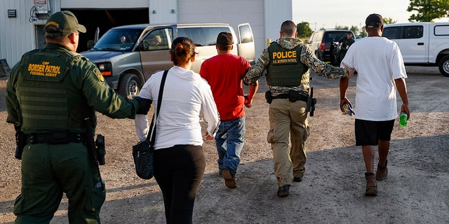 Government agents take suspects into custody during an immigration sting at Corso's Flower and Garden Center in Castalia, Ohio, Tuesday.