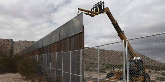 In this Nov. 10, 2016 file photo, workers raise a taller fence along the Mexico-US border between the towns of Anapra, Mexico and Sunland Park, New Mexico