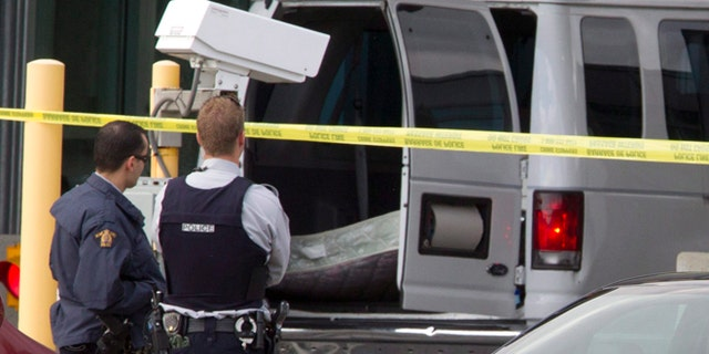 Oct. 16, 2012: Police investigate a van at the scene of a shooting at the Blaine, Wash./Surrey, British Columbia border crossing in Surrey.