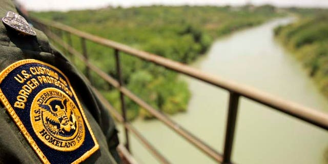 FILE: A Border Patrol agent looks over the Rio Grande  with Mexico on the left and the U.S. on the right from a railroad bridge in Laredo.