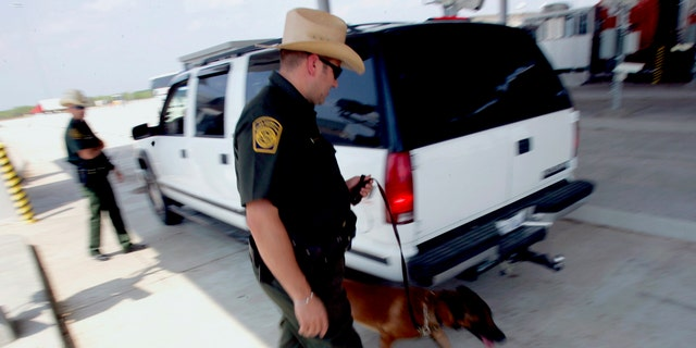 U.S. Border Patrol agents check a car's occupants and use a dog to sniff out drugs at a checkpoint coming into the U.S. outside Laredo, Texas