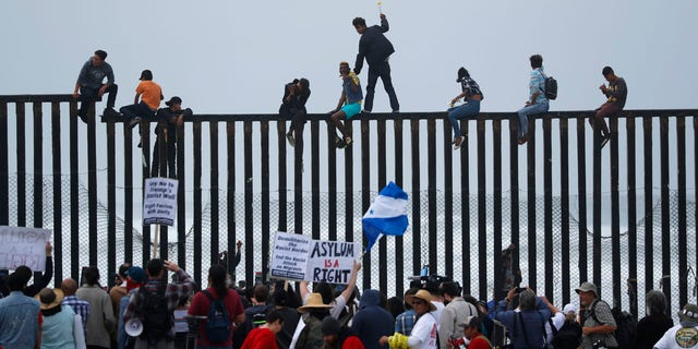 People climb the border wall fence as a caravan of migrants and supporters reached the United States-Mexico border near San Diego, California, U.S., April 29, 2018.